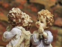 Primer de una estatua de un pequeño ángel que ruega imagen de archivo