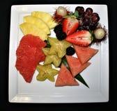 Primer de una exhibición de la fruta fresca cortada, de las bayas enteras y de las uvas exhibidas en una placa blanca Imagenes de archivo