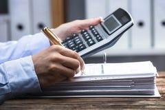 Primer de una factura calculadora de la mano del ` s del empresario foto de archivo libre de regalías