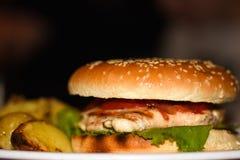 Primer de una hamburguesa con el pollo, la ensalada y las patatas en una placa blanca en una tabla en un café en un fondo oscuro foto de archivo libre de regalías