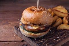 Primer de una hamburguesa sabrosa con bocados bajo la forma de patatas con la salsa de ajo blanca Hamburguesa jugosa con los anil Imagenes de archivo