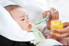 Primer de una madre que da el alimento a su bebé lindo fotos de archivo