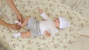 Primer de una mamá joven que viste a su bebé recién nacido en la cama en el dormitorio almacen de metraje de vídeo