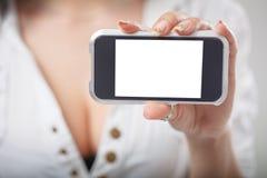 Primer de una mano de la muchacha que muestra un sc en blanco horizontal del smartphone Fotografía de archivo libre de regalías