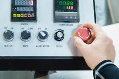 Primer de una mano del ` s del hombre en un botón rojo en el panel de control  Parada de emergencia o comienzo del equipo y de la foto de archivo