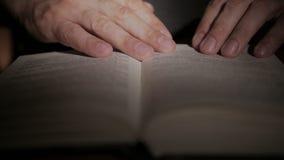 Primer de una mano del ` s del hombre que sostiene un libro de papel abierto, dando vuelta a las páginas con sus fingeres almacen de metraje de vídeo