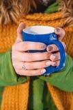 Primer de una mano del ` s de la mujer que sostiene una taza de café caliente imagen de archivo