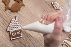 Primer de una mano femenina mientras que adorna el pan de jengibre de la Navidad en una tabla de madera Fotografía de archivo libre de regalías