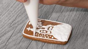Primer de una mano femenina mientras que adorna el pan de jengibre lindo en una tabla de madera Imagen de archivo libre de regalías