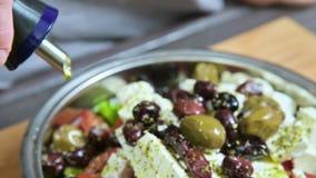 Primer de una mano femenina que riega el aceite de oliva fresco de la ensalada del Griego del vegano Forma de vida sana de la com metrajes