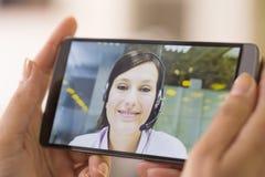 Primer de una mano femenina que sostiene un teléfono elegante durante Skype VI fotos de archivo libres de regalías