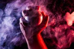Primer de una mano masculina fuerte que sostiene una bola blanca del béisbol fotografía de archivo