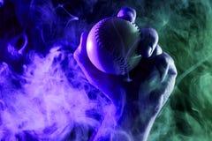 Primer de una mano masculina fuerte que sostiene una bola blanca del béisbol fotografía de archivo libre de regalías