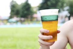 Primer de una mano masculina que sostiene la cerveza con la piscina borrosa i imagen de archivo