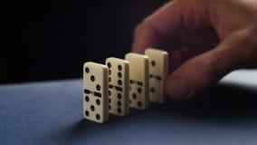 Primer de una mano que pone un dominó El caer de los dominós Nervioso y fracaso almacen de video