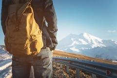 Primer de una mochila en la parte posterior de un viajero masculino que camina a lo largo de una carretera nacional en el fondo d Imagen de archivo