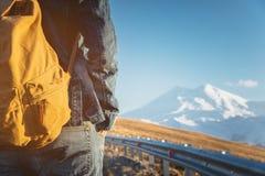 Primer de una mochila en la parte posterior de un viajero masculino que camina a lo largo de una carretera nacional en el fondo d Imágenes de archivo libres de regalías