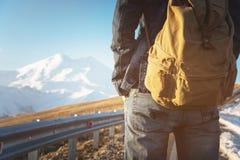 Primer de una mochila en la parte posterior de un viajero masculino que camina a lo largo de una carretera nacional en el fondo d Imagen de archivo libre de regalías