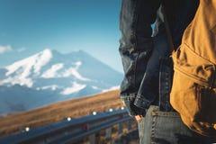 Primer de una mochila en la parte posterior de un viajero masculino que camina a lo largo de una carretera nacional en el fondo d Foto de archivo libre de regalías