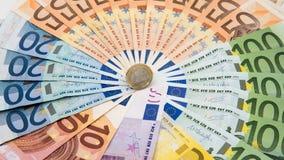 Primer de una moneda un euro con los billetes de banco de diversos valores Cobre el dinero fotos de archivo