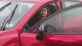Primer de una muchacha asustada que se sienta en el coche despu?s de un accidente bajo la lluvia metrajes