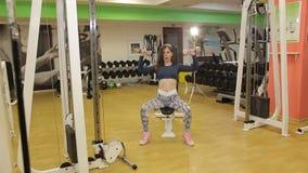 Primer de una muchacha atlética joven con los trenes de una pesa de gimnasia del metal en el gimnasio almacen de video