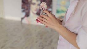 Primer de una muchacha del artista que limpia sus manos en el trapo almacen de metraje de vídeo