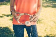 Primer de una muchacha delgada en una camiseta roja que guarda el headp blanco Foto de archivo
