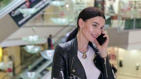 Primer de una muchacha en una chaqueta de cuero que habla en el teléfono en un centro comercial almacen de metraje de vídeo