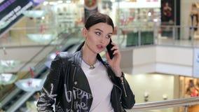 Primer de una muchacha en una chaqueta de cuero que habla en el teléfono en un centro comercial almacen de video