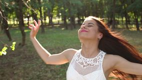 Primer de una muchacha feliz con el pelo que fluye que camina en un parque del verano en la puesta del sol metrajes