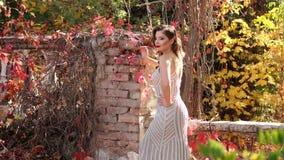 Primer de una muchacha hermosa con maquillaje brillante que camina en parque del otoño metrajes