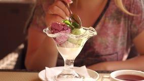 Primer de una muchacha que come el helado de un vidrio hermoso en un café de la calle metrajes