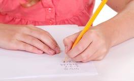 Primer de una muchacha que hace los problemas de matemáticas Imagen de archivo libre de regalías