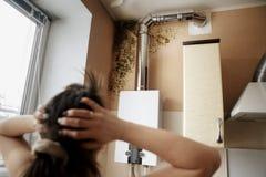 Primer de una mujer chocada que mira el molde en la pared Foto de archivo