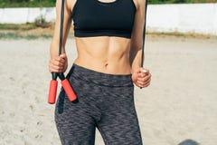 Primer de una mujer deportiva joven en la ropa de deportes que sostiene un esquí rojo Imágenes de archivo libres de regalías