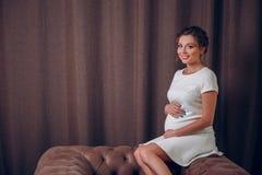 Primer de una mujer embarazada que toca su estómago suavemente mientras que se sienta en una butaca imagen de archivo libre de regalías