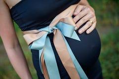 Primer de una mujer embarazada que toca su vientre con las manos Fotografía de archivo libre de regalías