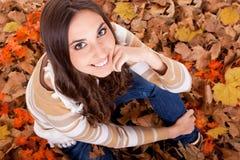 Primer de una mujer en hojas de otoño Fotos de archivo libres de regalías