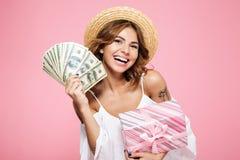 Primer de una mujer feliz joven en sombrero de paja, llevando a cabo el bil del dólar Imagen de archivo libre de regalías