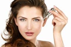 Primer de una mujer hermosa que aplica un tratamiento de la belleza Imágenes de archivo libres de regalías