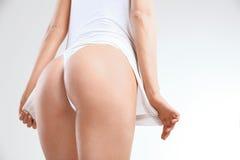Primer de una mujer hermosa que muestra las nalgas perfectas en blanco Foto de archivo
