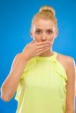 Primer de una mujer joven hermosa con la boca de la cubierta de la mano. Foto de archivo libre de regalías