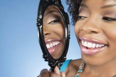 Primer de una mujer joven que mira se en espejo y que sonríe sobre fondo coloreado Imagen de archivo libre de regalías