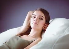 Primer de una mujer joven sonriente que miente en el sofá Imágenes de archivo libres de regalías