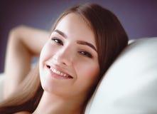 Primer de una mujer joven sonriente que miente en el sofá Foto de archivo libre de regalías
