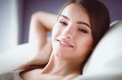 Primer de una mujer joven sonriente que miente en el sofá Fotos de archivo