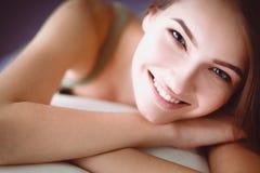 Primer de una mujer joven sonriente que miente en el sofá Imagen de archivo libre de regalías
