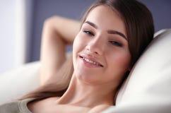 Primer de una mujer joven sonriente que miente en el sofá Imagen de archivo