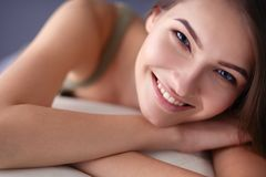 Primer de una mujer joven sonriente que miente en el sofá Fotografía de archivo